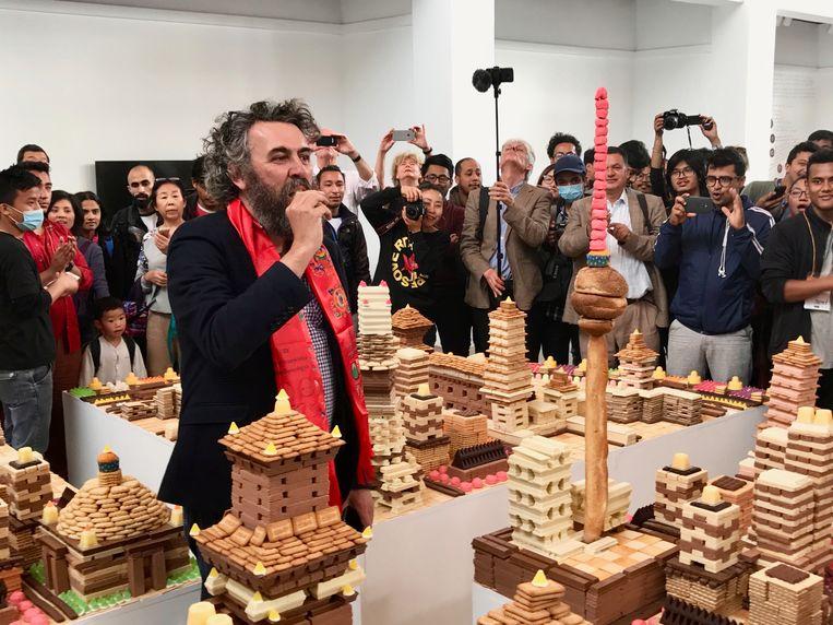 De curator begint onder grote belangstelling een uit snoep en koekjes opgetrokken stadsmaquette van de Chinese kunstenaar Song Dong op te eten. Beeld rv Ben Van Alboom