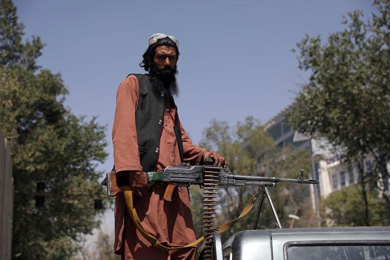 Een talibanstrijder houdt de wacht bij het presidentieel paleis in Kaboel.  Beeld AP