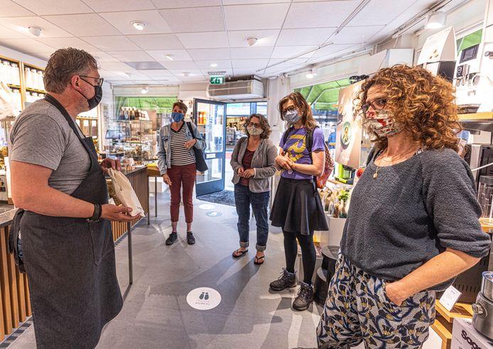 Deelnemers aan de toer krijgen bij Simon Lévelt in Zwolle uitleg over hoe je een katoenen koffiezakje steeds opnieuw kunt gebruiken voor je aankopen.