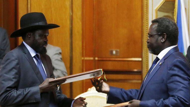 President Salva Kiir en rebellenleider Riek Machar ondertekenen het vredesakkoord.