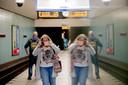 Een vrouw in Berlijn doet een mondmasker op bij metrostation Turmstrasse.
