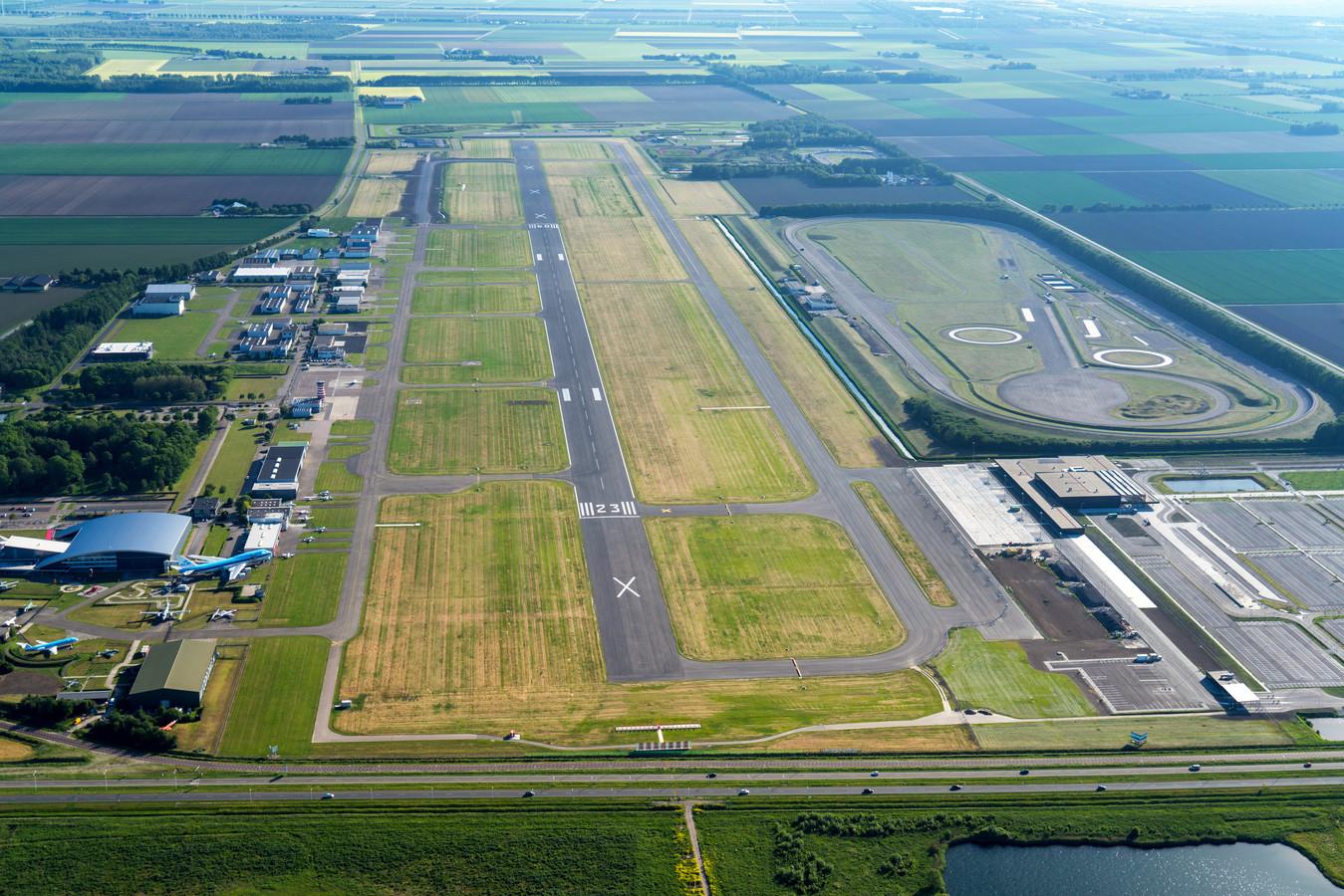 Luchtfoto met in het midden de verlengde start- en landingsbaan en rechts de nieuwe passagiersterminal.