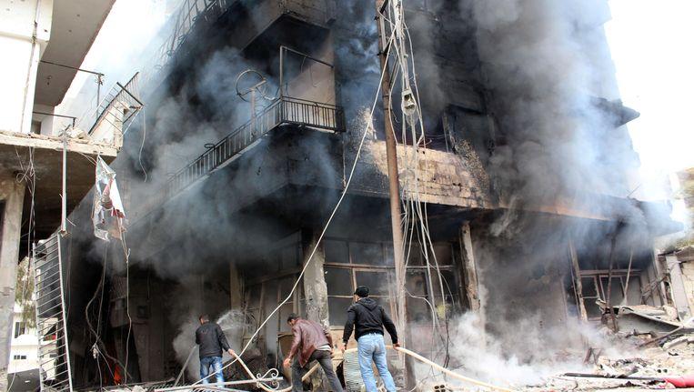 Mannen proberen een brand in een gebouw in Damascus te blussen. Beeld AFP