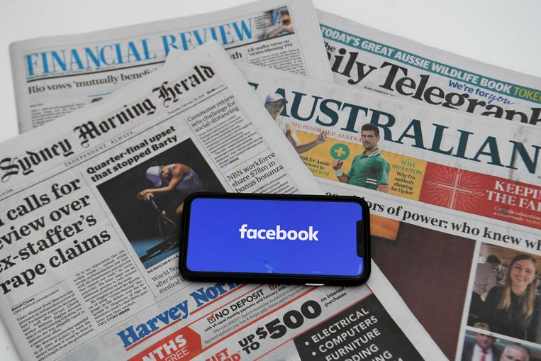 Australische kranten met het logo van Facebook op een mobiele telefoon. Beeld REUTERS
