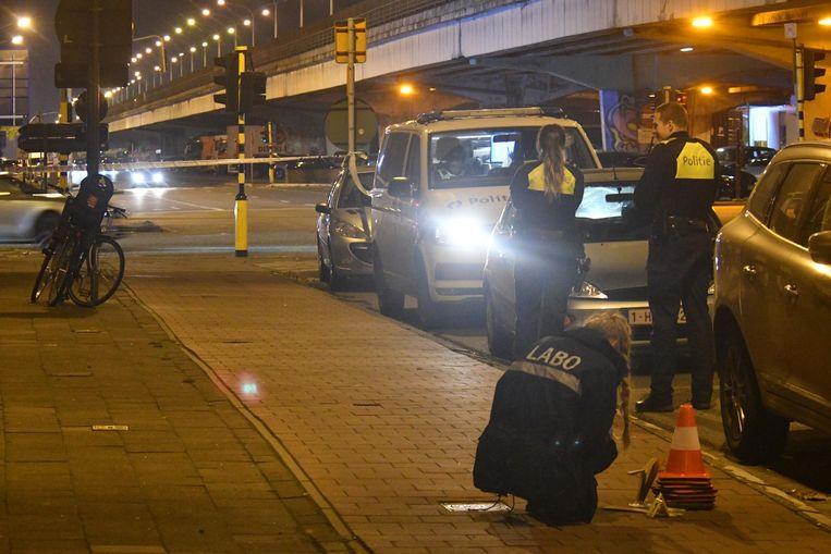 Een medewerkster van het labo onderzoekt de plaats van de schietpartij, die afgezet werd door de politie.