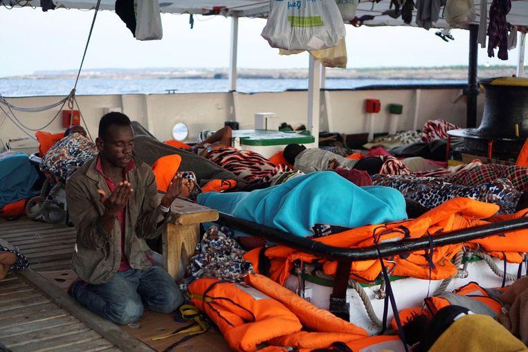 Deze migrant aan boord van het schip bidt dat alles snel voorbij is.  Beeld EPA