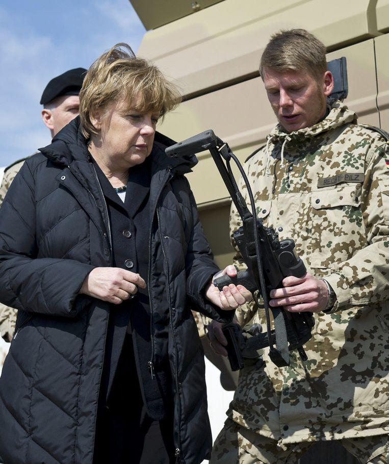 Angela Merkel inspecteert tijdens een reis naar Afghanistan in 2012 een Heckler & Koch MP7 machinegeweer. Een ander wapen heeft problemen in warme klimaten. Beeld Reuters