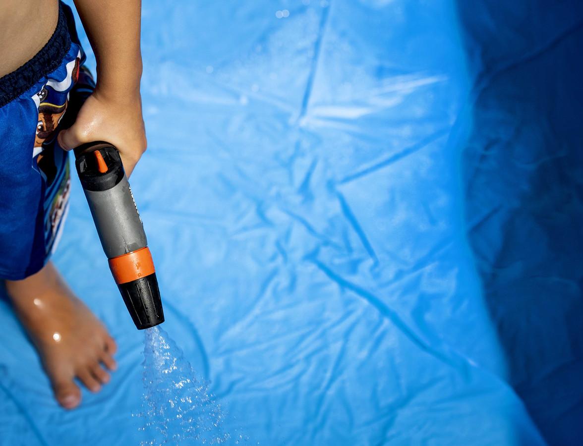 Een jongetje vult zijn opblaaszwembadje met water.