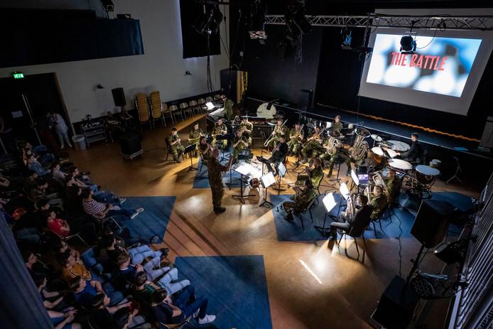 Leerlingen van het Sint-Janslyceum kijken naar de film, de fanfare maakt muziek.