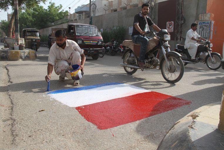 Een man schildert een Nederlandse vlag op de weg in Hyderabad, Pakistan uit protest tegen Geert Wilders' cartoonwedstrijd. Beeld EPA