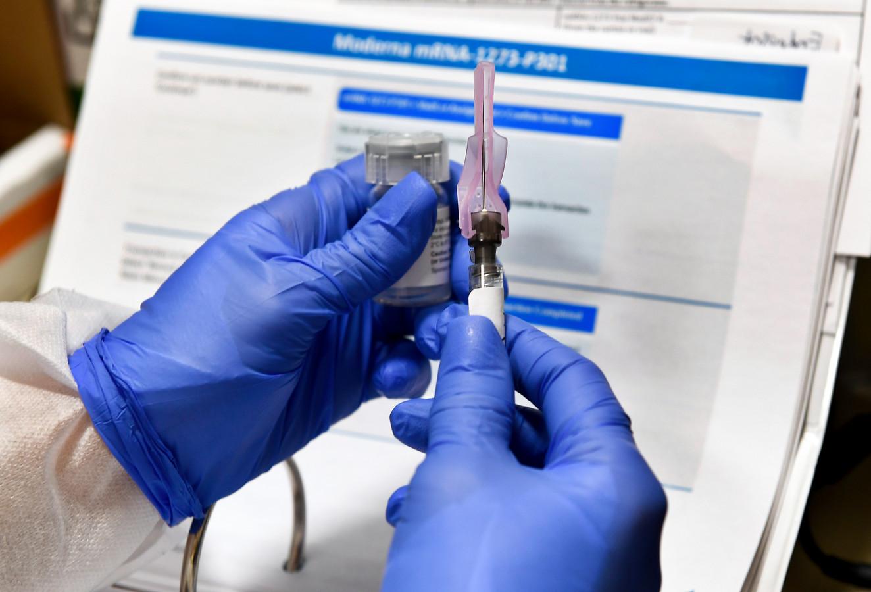 Een verpleger in New York maakt een dosis van het Moderna-vaccin gereed voor gebruik.