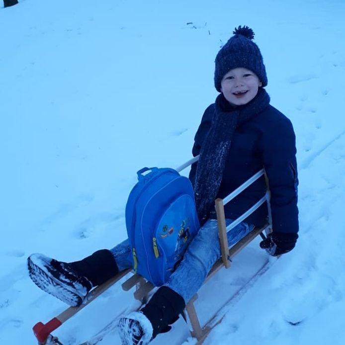 Siem in de sneeuwtaxi op weg naar school in Breedeweg.