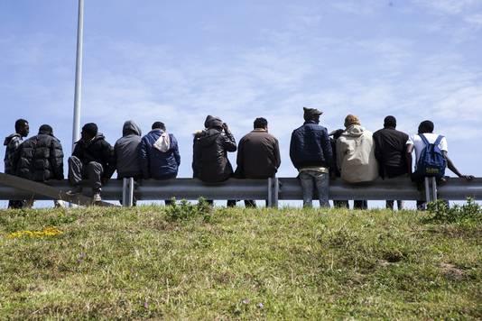 Migranten wachten op de vangrail naast de toegangsweg naar de tunnel