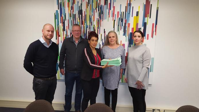 Leden van de actiegroep die zich verzet tegen de huisvesting van 100 arbeidsmigranten in Glorieux in Dongen overhandigen de petitie aan wethouder Bea van Beers (r.).