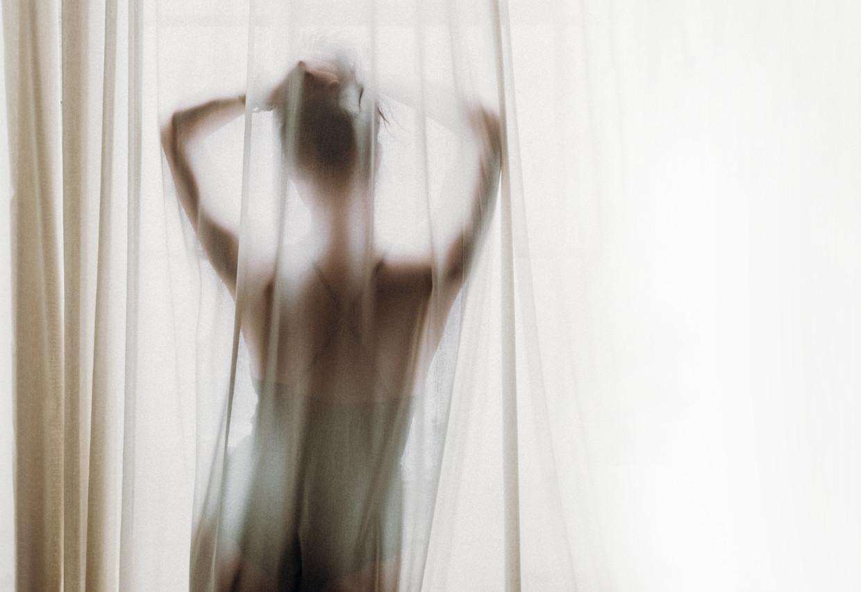 Woman curtains Beeld Unsplash