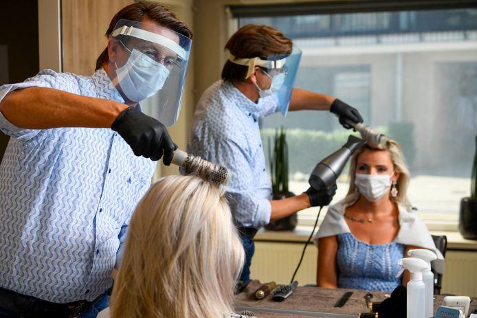 Beeld ter illustratie. Zo mag het in de toekomst dus niet meer. De klant moet minimaal een chirurgisch mondmasker dragen, de kapper mogelijks zelfs een FFP2-masker.