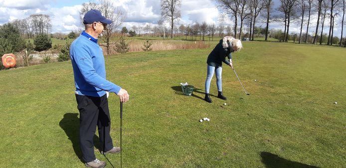Hennie van der Duin van golfclub De Koepel leert Ellemijn Pas om te chippen.