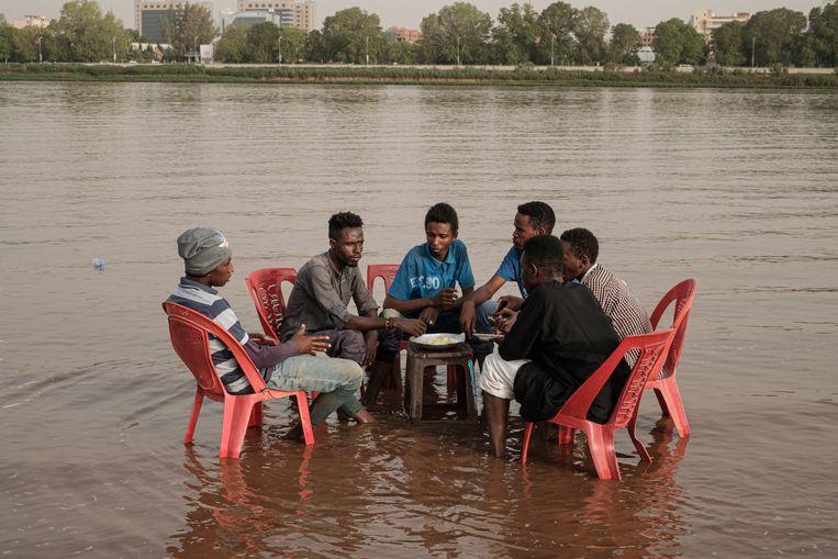 Soedanezen delen een maaltijd vlakbij Khartoem.  Beeld AFP