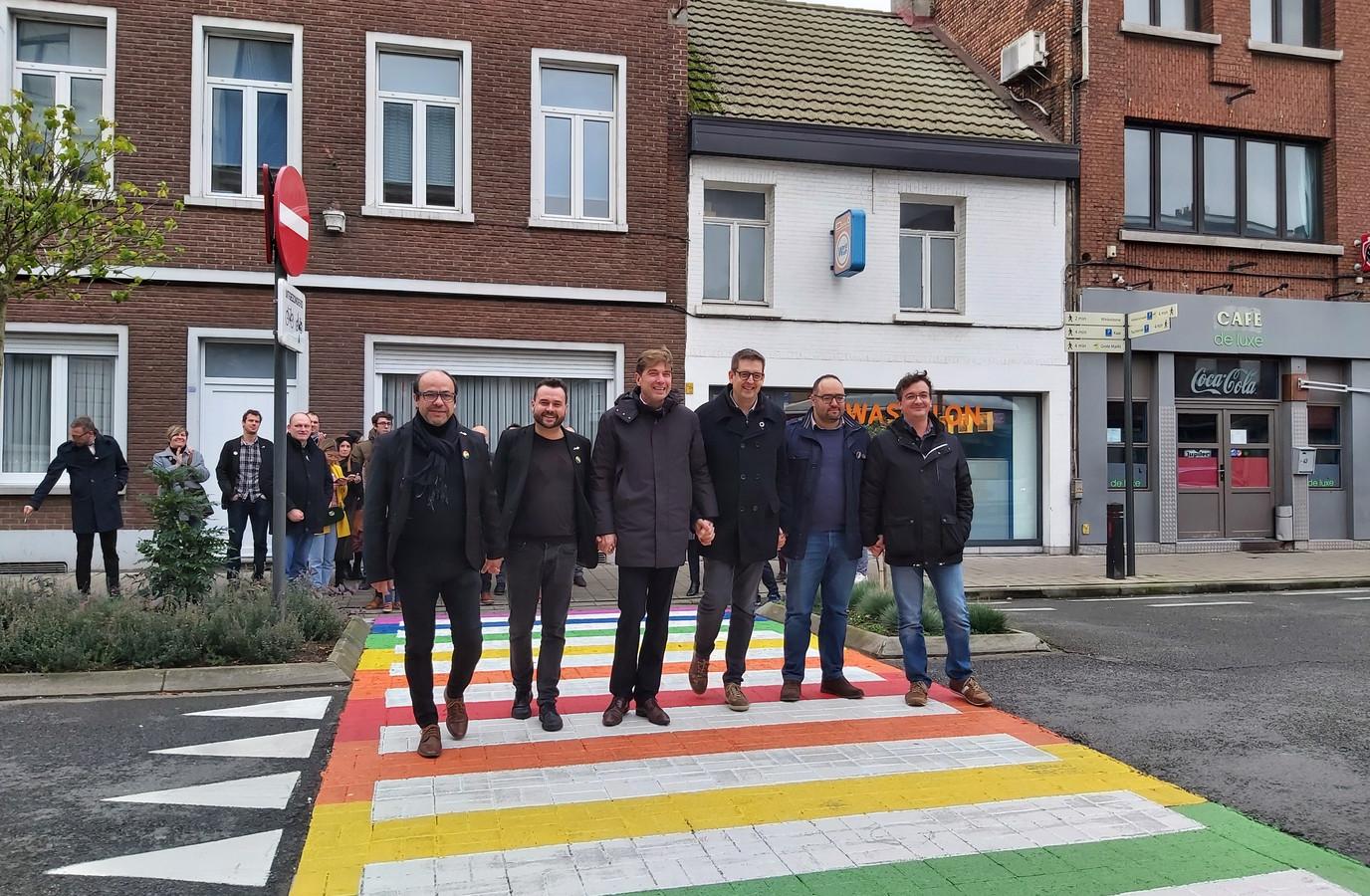 Het gemeentebestuur van Boom, samen met Gregory Frateur (tweede van links), wandelt het regenboogzebrapad in.
