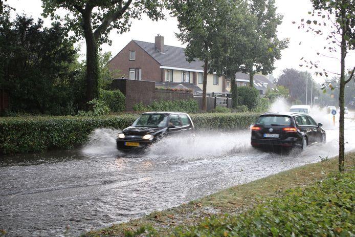 Auto's waden door het water op de Lunterseweg in Barneveld.