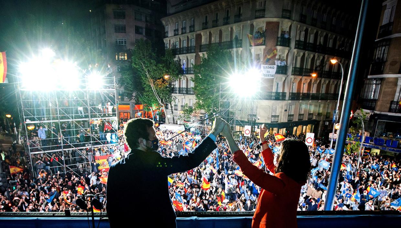Regiopresident Isabel Diaz Ayuso (rechts) en de leider van de Volkspartij Leader Pablo Casado (links) vieren hun verkiezingsoverwinning. Beeld EPA