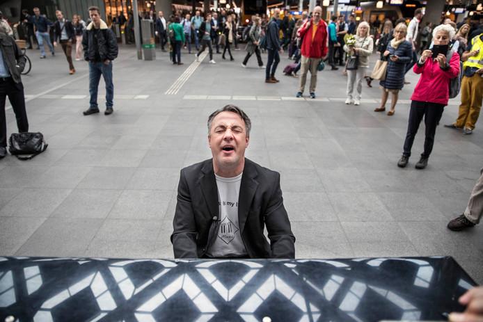 De Zwolse stationspianist Hans Jansen op station Den Haag CS tijdens zijn recordpoging om alle 16 stationspiano's in Nederland te bespelen. Foto Frank Jansen