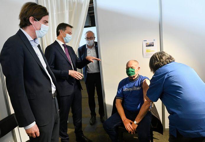 Burgemeester De Clercq, premier De Croo en schepen Coddens kijken toe hoe een man zijn vaccin krijgt