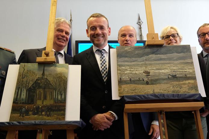 In het midden Axel Rüger met de twee schilderijen.
