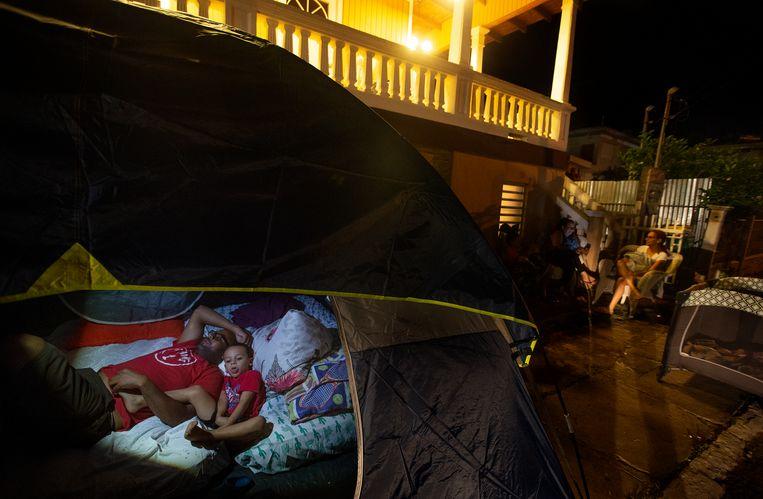 Een familie uit Guayanilla, op Puerto Rico, slaapt in een tent buiten, uit angst voor nieuwe schokken. Beeld Getty Images