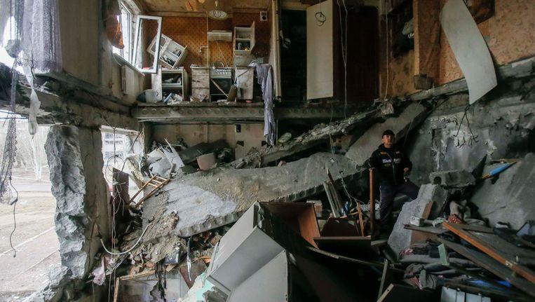 Een man in het plaatsje Jenakieve, niet ver van het belegerde Debaltseve in Oost-Oekraïne, bekijkt de chaos in een flat waarvan de vloer is ingezakt na een raketinslag. Beeld REUTERS