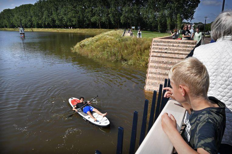 De nieuwe hoogwatergeul bij Ooijen is volgelopen met Maaswater. Een watersporter maakt er dankbaar gebruik van. Beeld Marcel van den Bergh / de Volkskrant