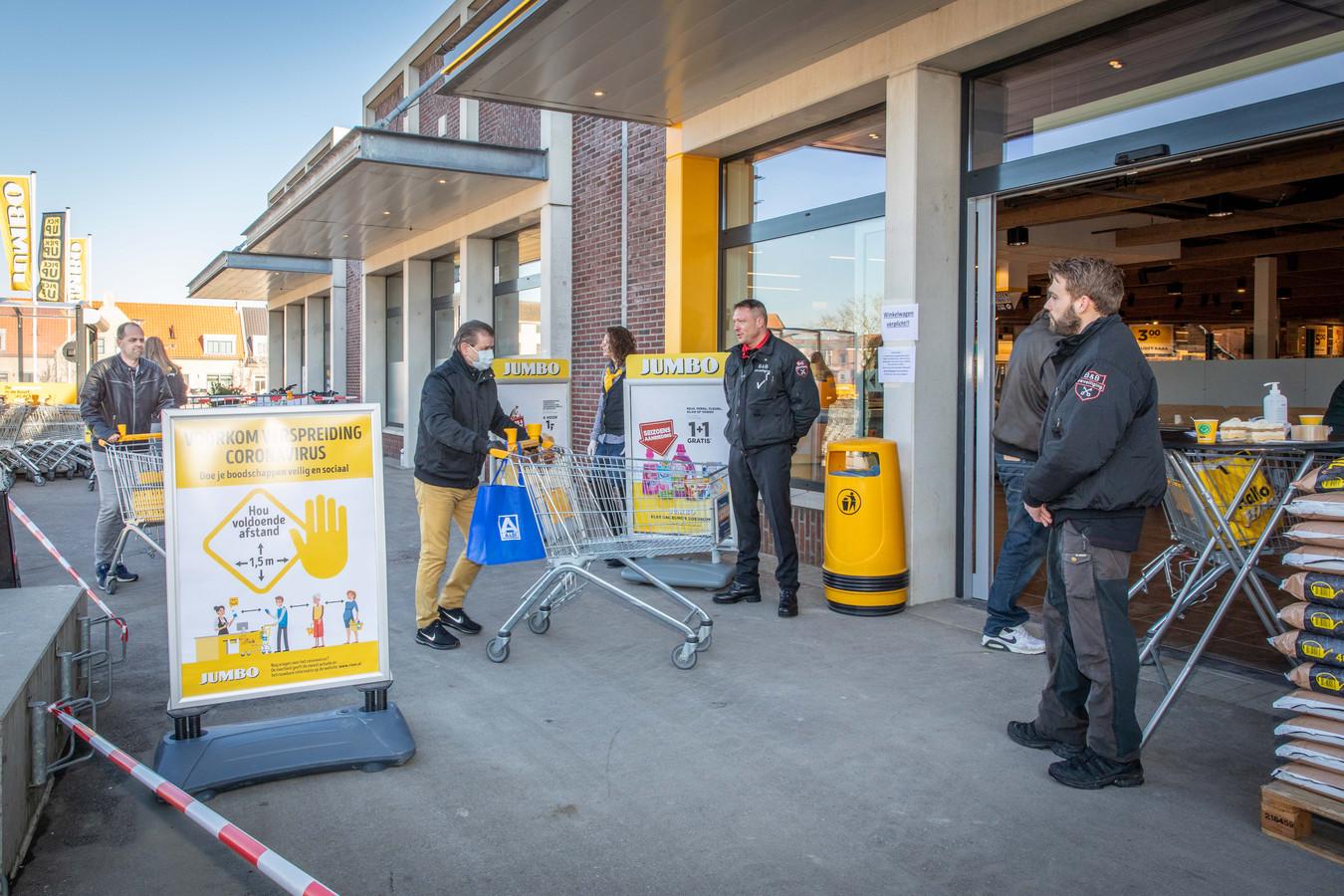 Toezicht bij de ingang van een supermarkt in Sint-Annaland: mondkapjes, gedesinfecteerde karretjes en vooral voldoende afstand.