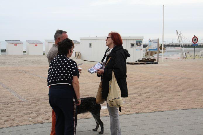Vrijwilligers delen de WC-rollen uit aan voorbijgangers op de Zeedijk in Nieuwpoort