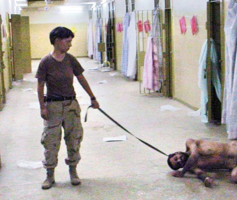 VS-militair Lynndie England houdt een naakte man aan de leiband in de Abu Ghraib-gevangenis in Irak (2003). Beeld EPA