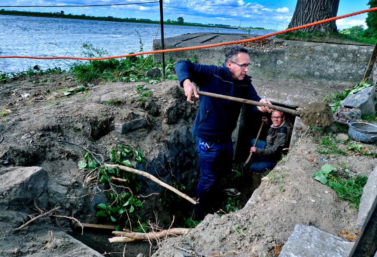 Wim Schrijvershof en Nick Vermaat van de Stichting Bunkerbehoud Dordrecht aan het werk in de loopgraaf naast de bunker.