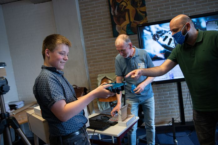 Ben van Elderen krijgt de prijs uitgereikt door Ali Dikici van Texas Instruments. Op de achtergrond wiskundedocent Paul van Gorsel, die Ben heeft gewezen op de landelijke programmeerwedstrijd.