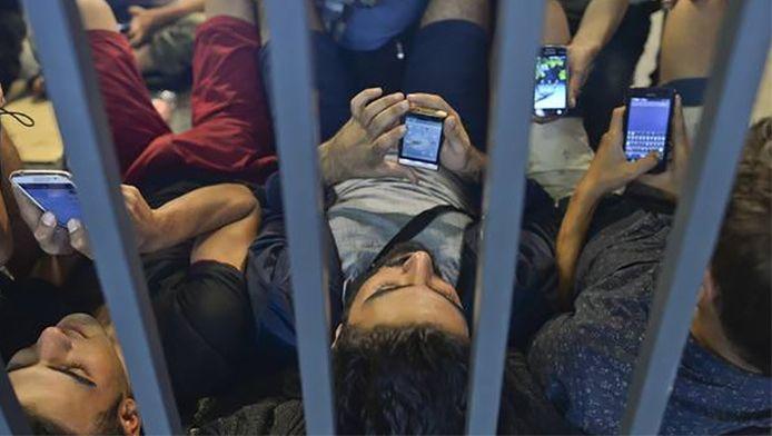 Vluchtelingen checken hun smartphone in het station van Boedapest.