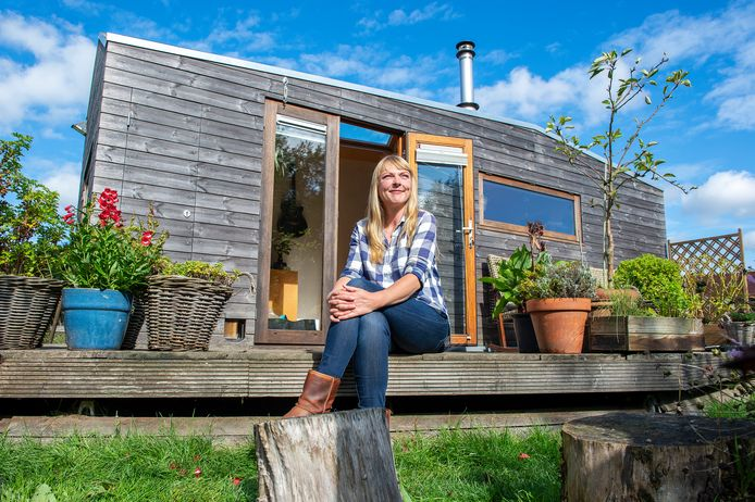 Marjolein Jonker zittend voor haar tiny house.