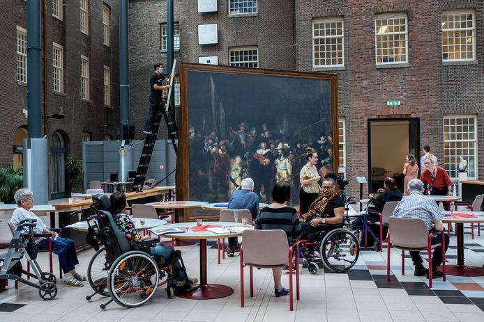 De bewoners van het Dr. Sarphatihuis in Amsterdam krijgen 'een rondleiding' (vanuit hun stoel).