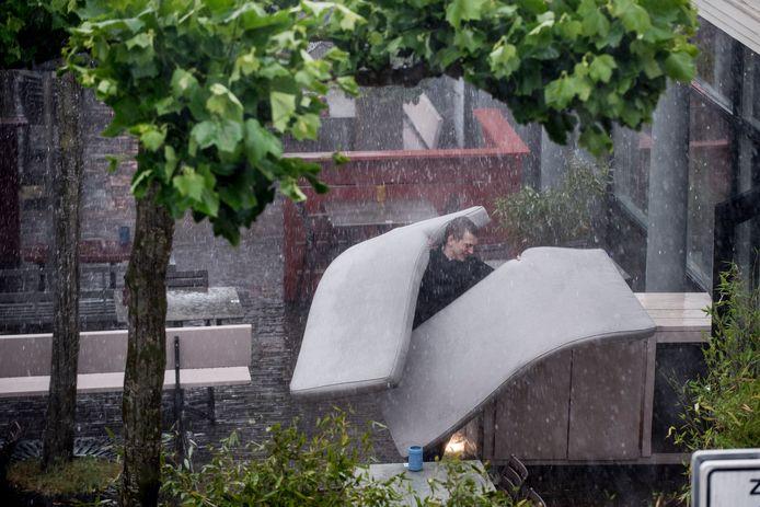 Horecamedewerker brengt kussen naar binnen, terwijl het stort van de regen.