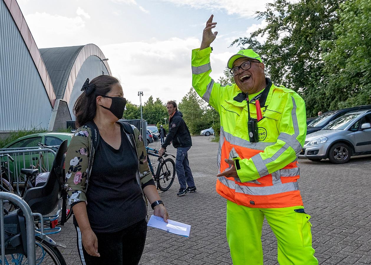 Parkeerregelaar Gene Jansen entertaint wanneer mensen komen voor een vaccinatie.