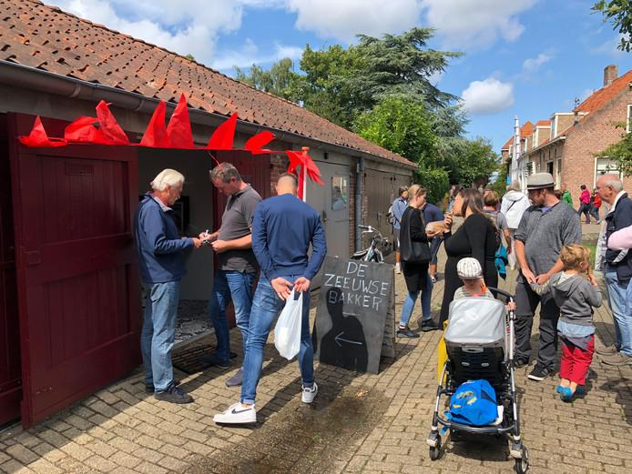 Ruud Backx (links) verzamelt namens de Stadsraad Veere handtekeningen bij klanten van de tijdelijke bakkerswinkel in een garagebox aan het Oranjeplein in Veere. Doel is een definitieve winkel te krijgen in het stadje.