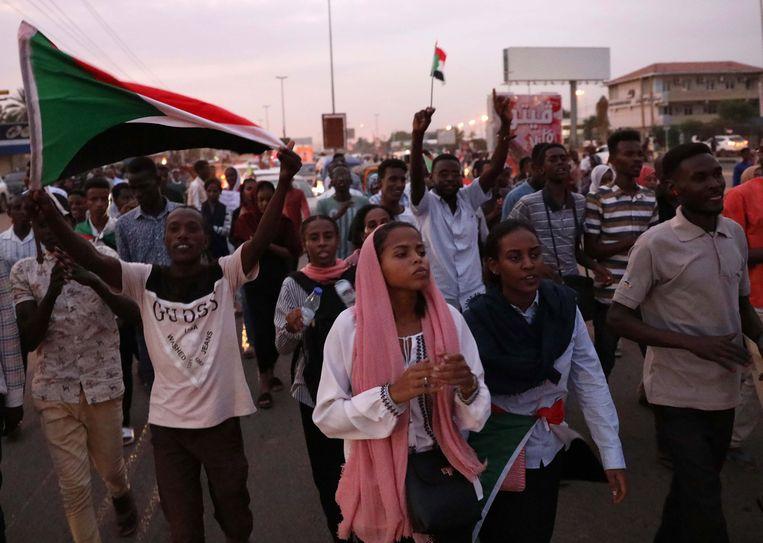 Soedanezen vieren het akkoord over de deling van de macht tussen militairen en burgers.  Beeld EPA