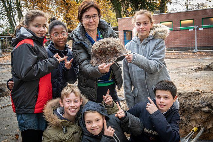 Juf Martine en enkele leerlingen uit het 6de met de opgegraven Duitse helm.