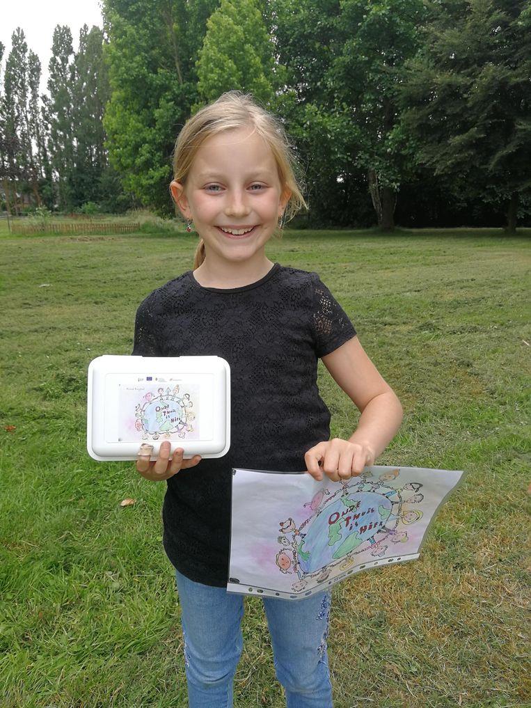 Fiona met haar winnende tekening en de brooddoos waarop die werd gedrukt.