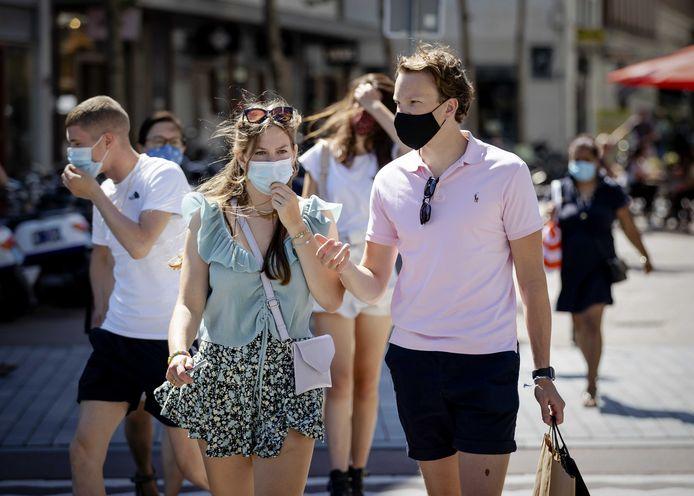 Mensen met mondkapjes in het centrum van Rotterdam. In een aantal winkelgebieden is zo'n kapje verplicht.