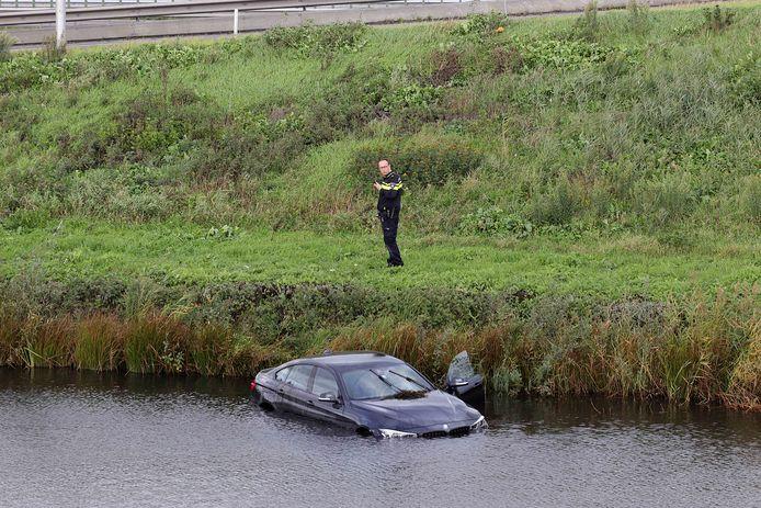 Man rijdt met zijn auto het water in langs de A59 bij Waalwijk.