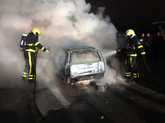 Auto in Veen wordt door brandweerlieden geblust.