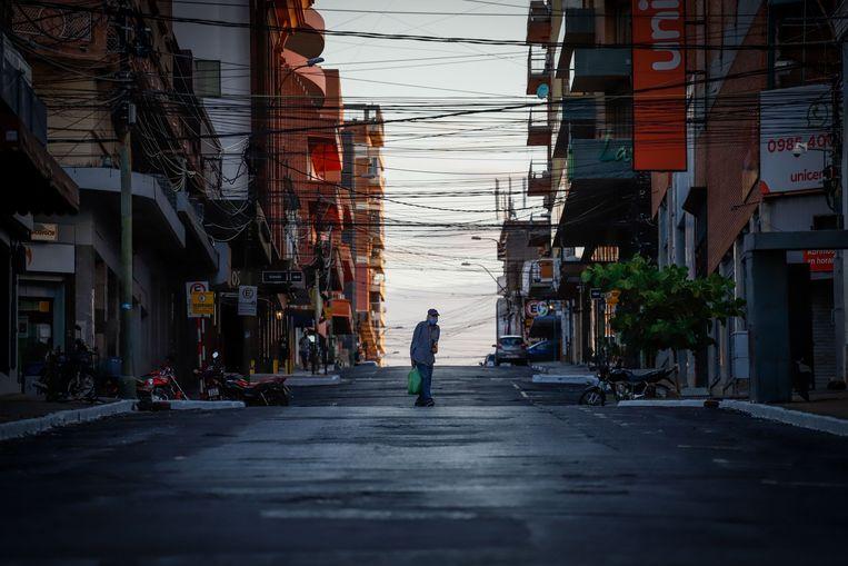 Een vrijwel lege straat in de Paraguayaanse hoofdstad Asunción, waar een strenge lockdown van kracht is. Beeld EPA
