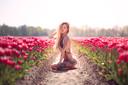 Danique de Laat (28) toont haar tattoos in een tulpenveld.